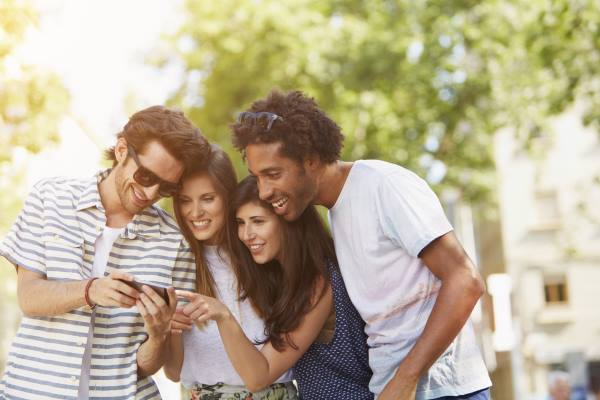 Happy young man sharing mobile phone with friends outdoors